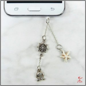 Audio jack dust plug, phone charm representing a beige starfish, a rudder and a pirate skull