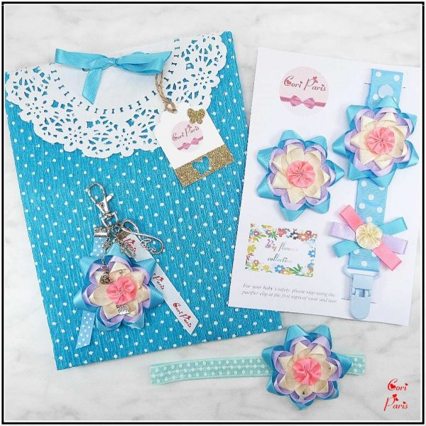 New mom gift set including a binky clip, barrette hair clip, headband and flower keychain