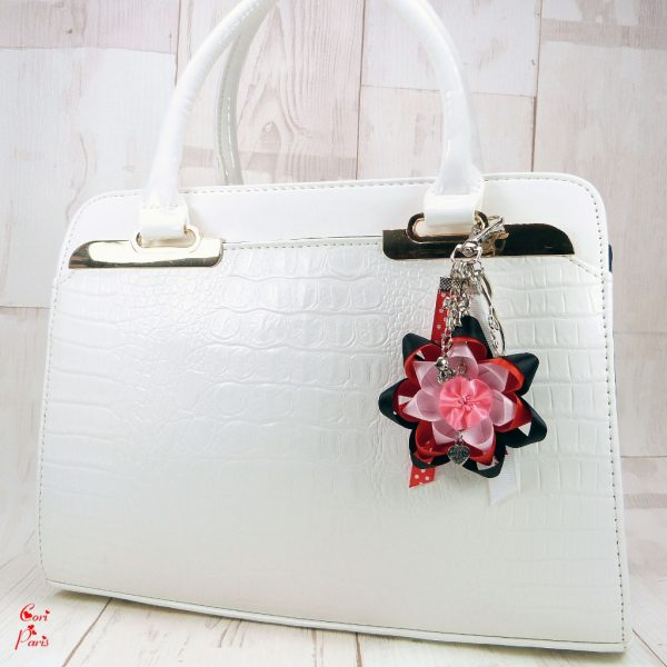 A cute bag charm with a large ribbon flower and baby charms to embellish your handbag