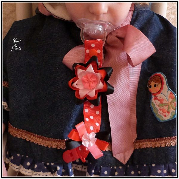 Baby girl pacifier clip with a red ribbon flower, original idea for a baby girl gift